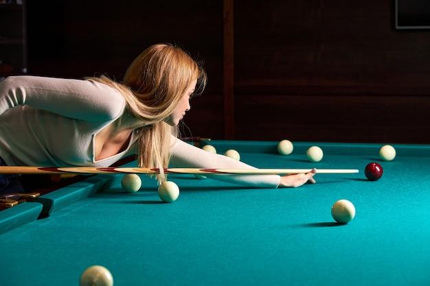 Frau, die sich über den tisch beugt, während sie snooker spielt, genießt die freizeit, billard zu spielen