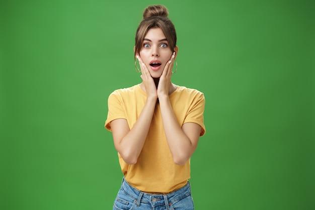 Frau, die sich überrascht und erfreut fühlt, ein gutes ergebnis nach der entgiftung zu genießen und eine hautpflegemaske aufzutragen, die die wangen berührt, den mund vor erstaunen öffnet und aufgeregt über der grünen wand posiert.