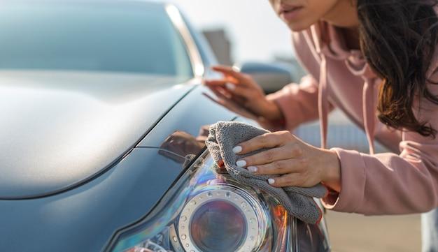Frau, die sich um ihr modernes auto kümmert