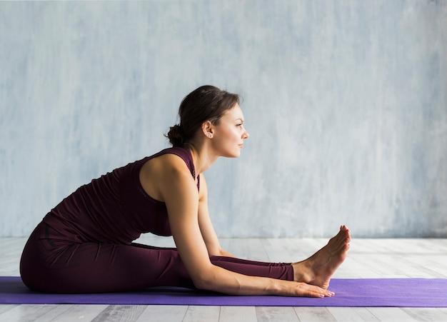 Frau, die sich vorwärts beim üben von yoga lehnt