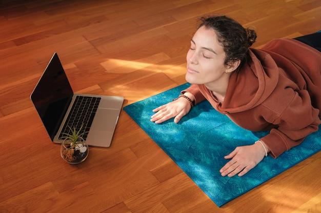 Frau, die sich während des online-yoga-kurses über eine matte streckt