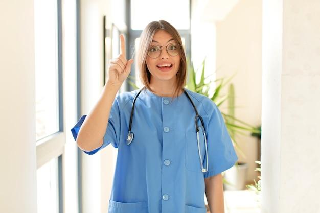 Frau, die sich wie ein glückliches und aufgeregtes genie fühlt, nachdem sie eine idee verwirklicht hat, fröhlich den finger hebt, heureka!