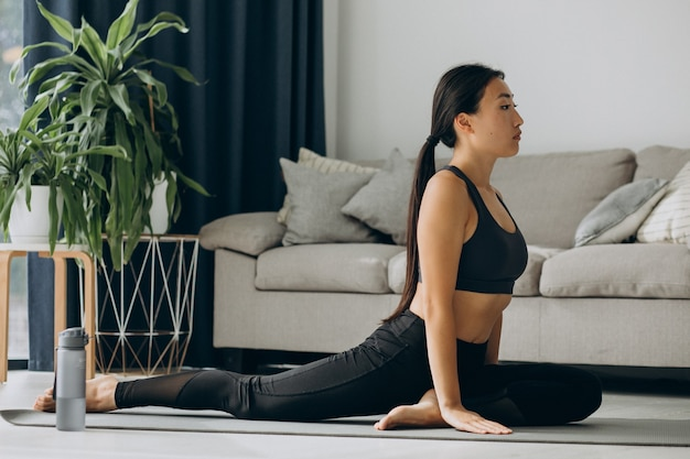 Frau, die sich zu hause auf yogamatte ausdehnt