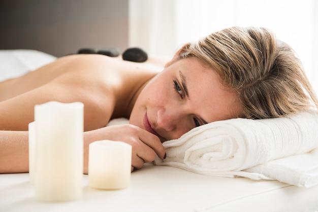 Frau, die sich zurück auf massagebett mit heißen steinen auf ihr entspannt