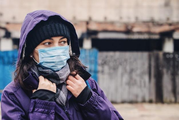 Frau, die sicherheitsmaske an der straße trägt. coronavirus-epidemie, lockdown. covid19 quarantäne. neues wirkliches leben während der pandemie. junge frau in der medizinischen maske im freien, um vor dem koronavirus geschützt zu werden.