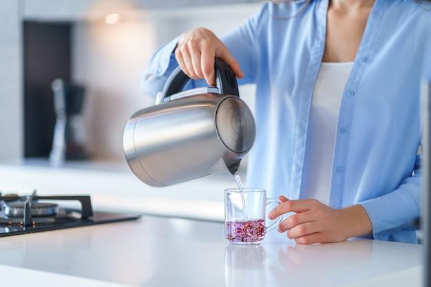 Frau, die silbermetall-wasserkocher für kochendes wasser und tee zu hause macht. haushaltsküchengeräte für macht heiße getränke
