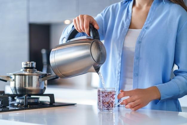 Frau, die silbermetall-wasserkocher für kochendes wasser und tee zu hause verwendet. haushaltsküchengeräte für macht heiße getränke