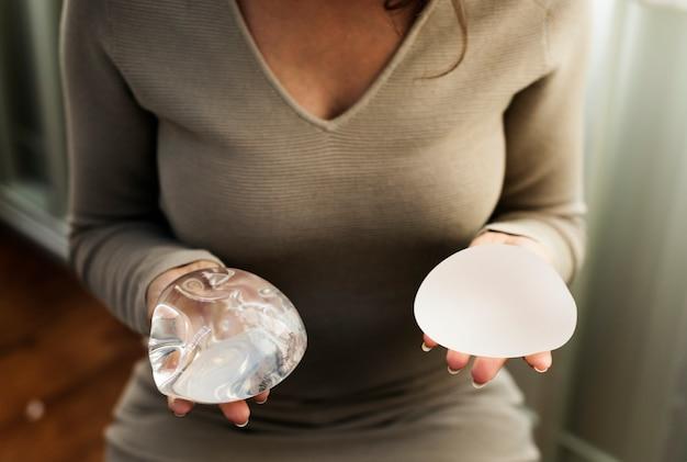 Frau, die silikonbeutel für brustimplantat hält