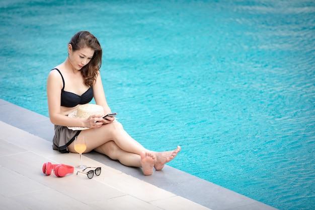 Frau, die smarthphone neben pool verwendet.