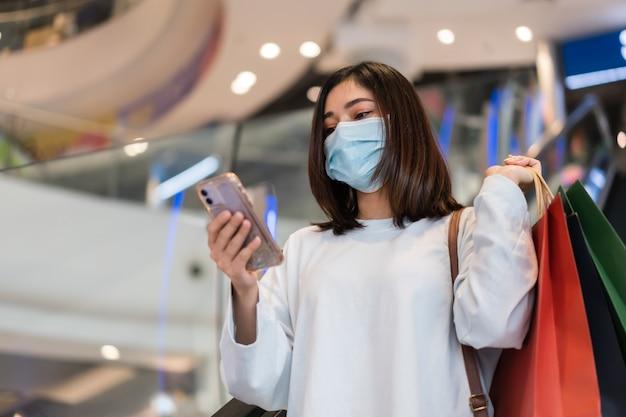 Frau, die smartphone am einkaufszentrum verwendet und medizinische maske zur verhinderung von coronavirus trägt