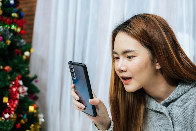 Frau, die smartphone auf ihrem bett in kaltem tag verwendet