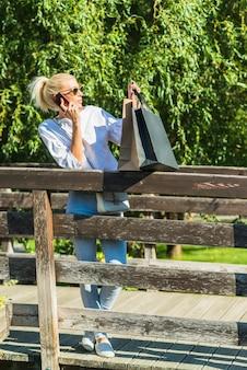 Frau, die smartphone auf steg spricht