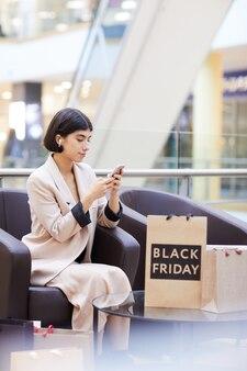 Frau, die smartphone beim entspannen im einkaufszentrum verwendet