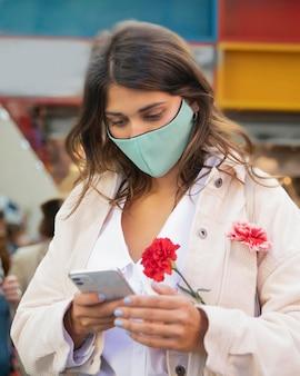 Frau, die smartphone beim halten von blumen verwendet