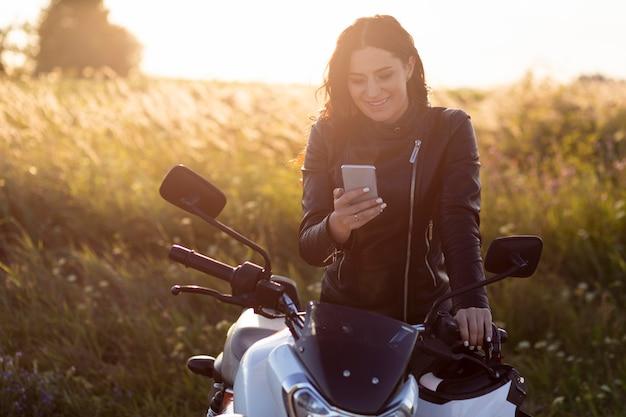 Frau, die smartphone beim sitzen auf ihrem motorrad betrachtet