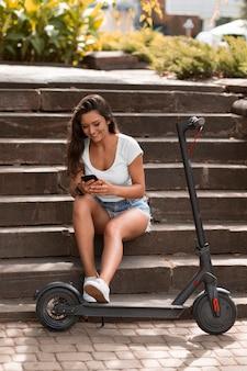 Frau, die smartphone beim sitzen auf stufen neben roller verwendet