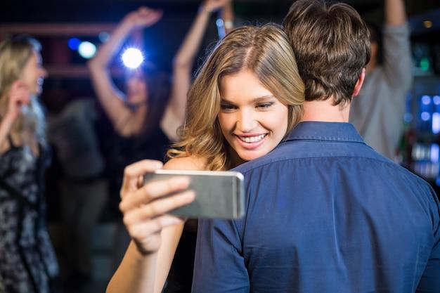 Frau, die smartphone beim umarmen des freundes verwendet
