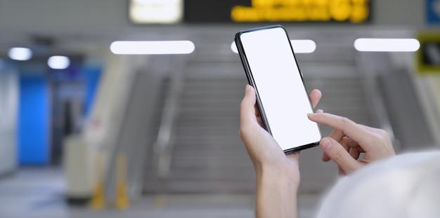 Frau, die smartphone des leeren bildschirms am bahnhof hält