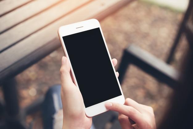Frau, die smartphone des leeren bildschirms verwendet. konzepte für die digitaltechnik im alltag.