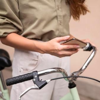Frau, die smartphone draußen mit fahrrad hält