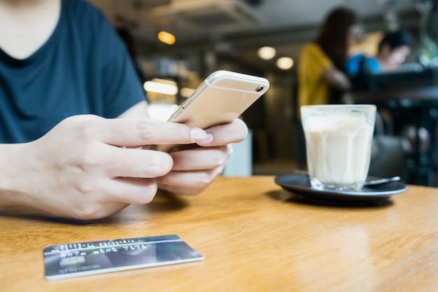 Frau, die smartphone für bewegliche transaktion verwendet oder online kauft