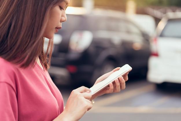 Frau, die smartphone für die anwendung auf autounschärfehintergrund verwendet.