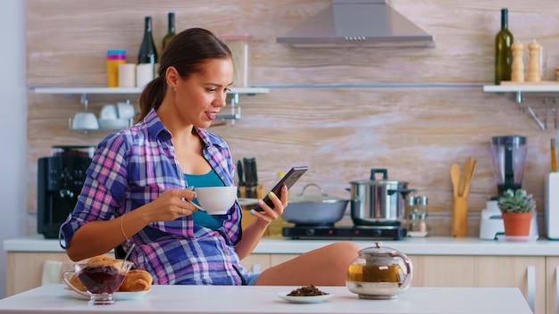 Frau, die smartphone für soziale medien verwendet und während des frühstücks eine tasse grünen tee in der küche trinkt. halten sie das telefongerät mit touchscreen mit internet-technologie, scrollen sie, suchen sie auf dem gadget
