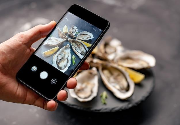Frau, die smartphone hält und frische austern mit zitrone auf schwarzem teller fotografiert