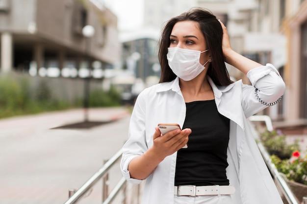 Frau, die smartphone hält und maske auf ihrem weg zur arbeit trägt