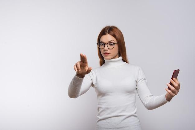 Frau, die smartphone hält und virtuellen knopf drückt