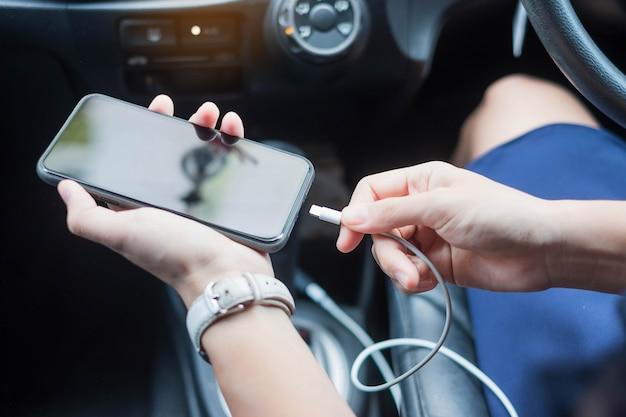 Frau, die smartphone im auto auflädt.