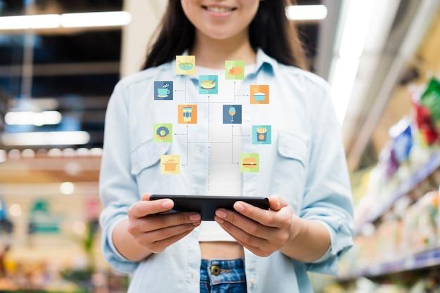 Frau, die smartphone im gemischtwarenladen verwendet
