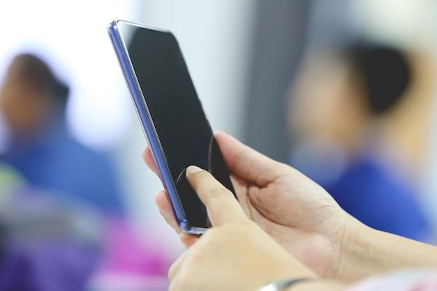 Frau, die smartphone im konferenzzimmer verwendet.