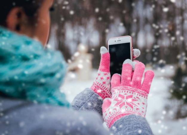 Frau, die smartphone im winter mit handschuhen für touchscreens verwendet