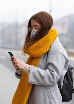 Frau, die smartphone in der stadt beim tragen der medizinischen maske verwendet