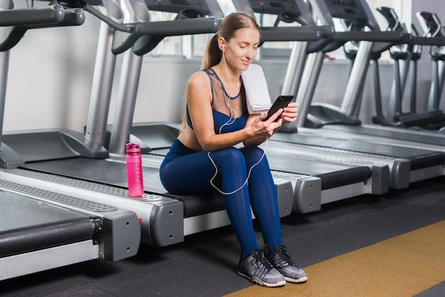 Frau, die smartphone in der turnhalle verwendet