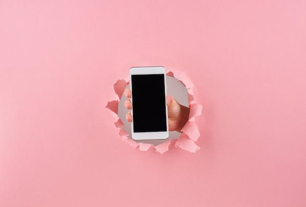 Frau, die smartphone in eingewickeltem loch im rosa hintergrund hält
