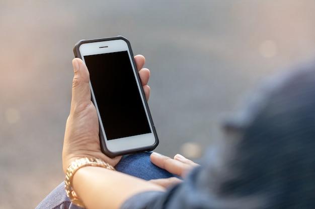 Frau, die smartphone mit dunklem schirm verwendet