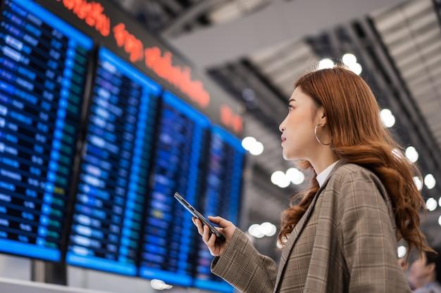 Frau, die smartphone mit fluginformationsbrett am flughafen verwendet