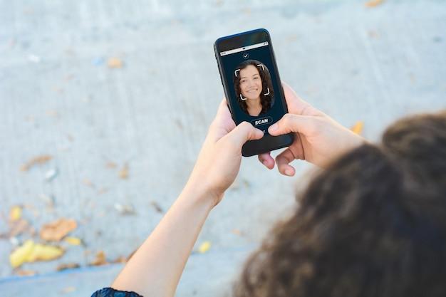 Frau, die smartphone mit gesichtserkennungstechnologie entriegelt
