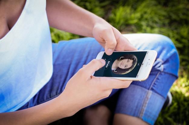 Frau, die smartphone mit gesichtserkennungstechnologie entsperrt