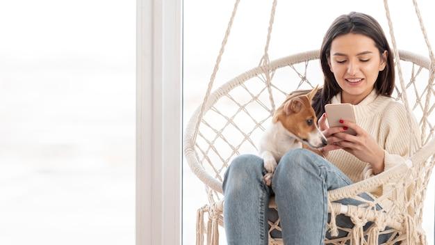 Frau, die smartphone mit ihrem hund betrachtet