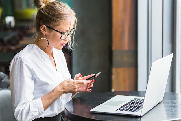 Frau, die smartphone mit laptop auf schreibtisch verwendet