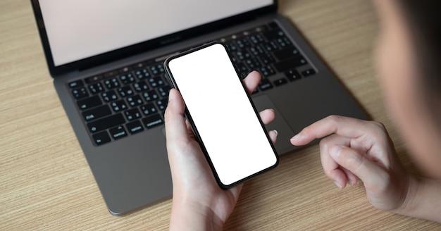 Frau, die smartphone mit leerem bildschirm am arbeitsplatz verwendet