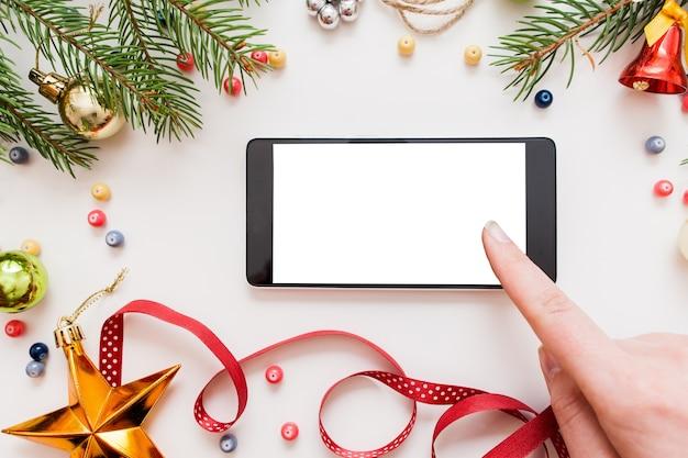 Frau, die smartphone mit leerem bildschirm auf tisch mit weihnachtsdekoration verwendet