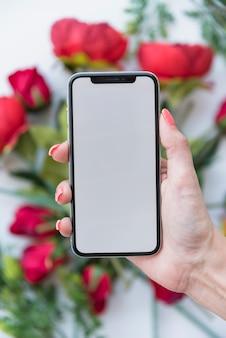 Frau, die smartphone mit leerem bildschirm über roten rosen hält