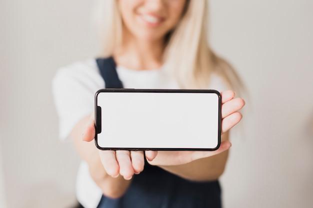 Frau, die smartphone mit modell hält