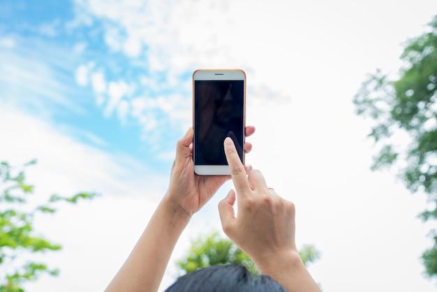 Frau, die smartphone mit unscharfem himmelhintergrund hält