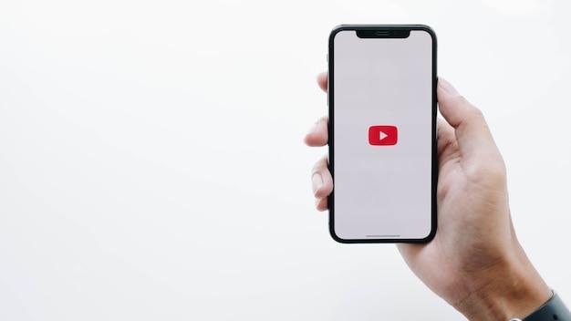 Frau, die smartphone mit youtube-app auf dem bildschirm hält