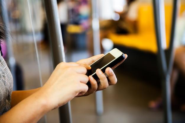 Frau, die smartphone, mobiltelefon in der u-bahn verwendet